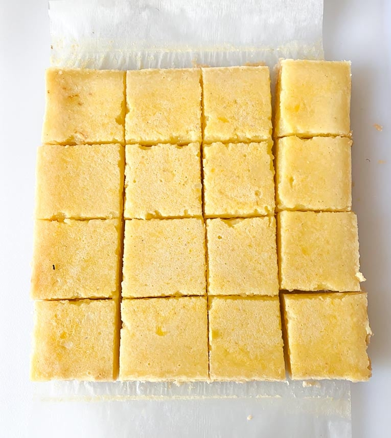 cutting lemon bars on a white board