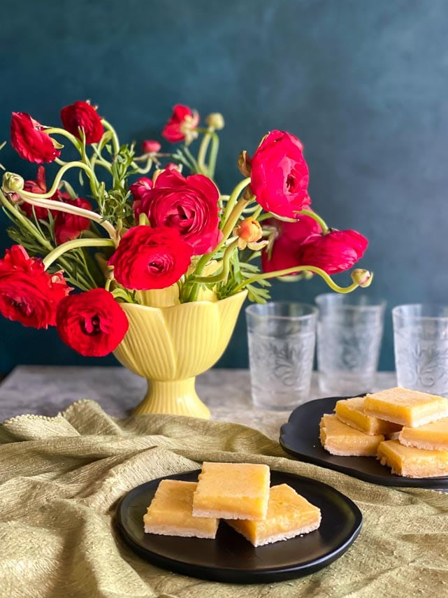 main vertical image of lemon bars on black plates with red ranunculus in yellow vase