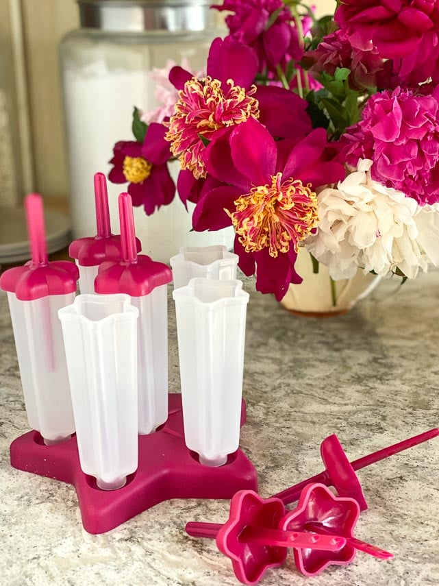 mold for popsicles on quartz surface, peonies in background