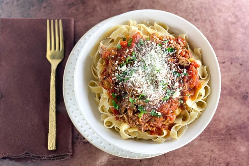 overhead Instant Pot Pork Ragu over noodles in white bowl on brown surface