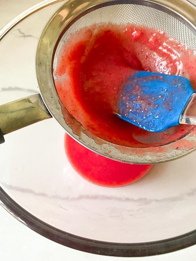 pressing strawberry purée through fine mesh strainer over glass bowl