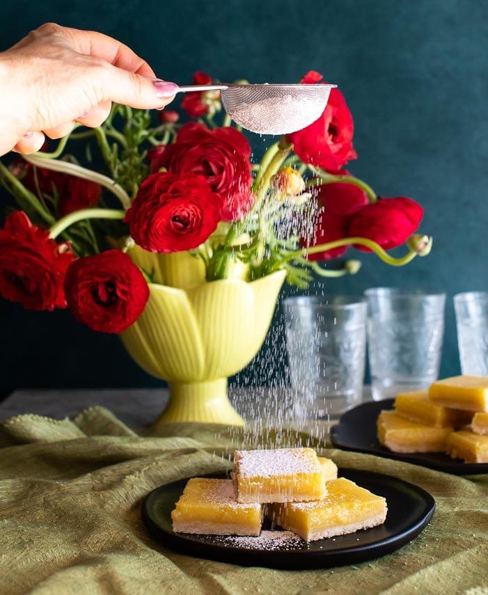 sifting confectioners sugar over lemon bars 2