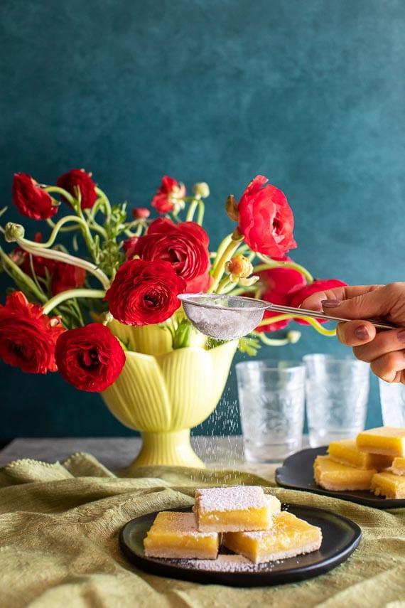 sifting confectioners sugar over lemon bars