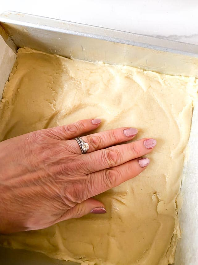 using hands to pat crust into 8-inch pan for lemon bars