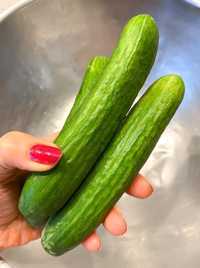 3 Persian cucumbers held in woman's hand