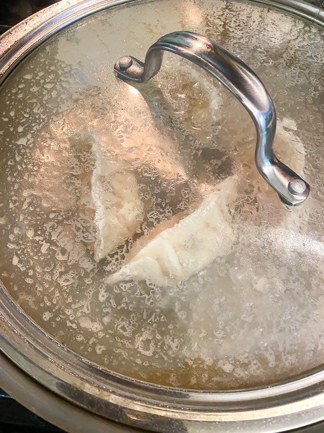 adding water to pan of seared dumplings; get the cover on quickly
