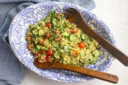 horizontal image of Low FODMAP Orzo Pasta Salad in blue and white oval bowl