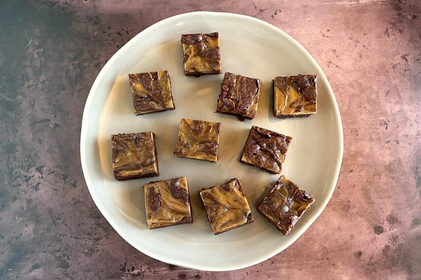 main image of espresso cream cheese brownies on light plate and brown background