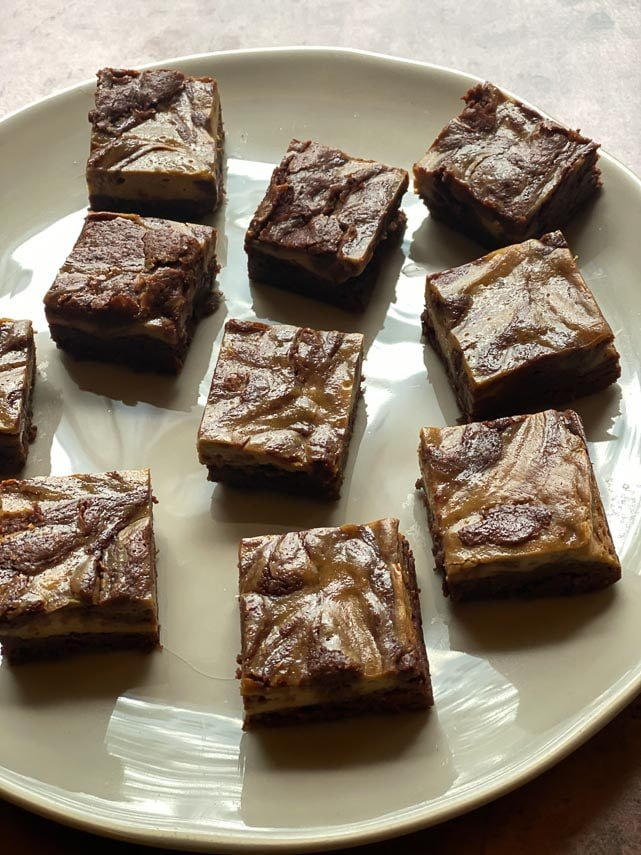 overhead vertical of espresso cream cheese brownies on light plate and brown background