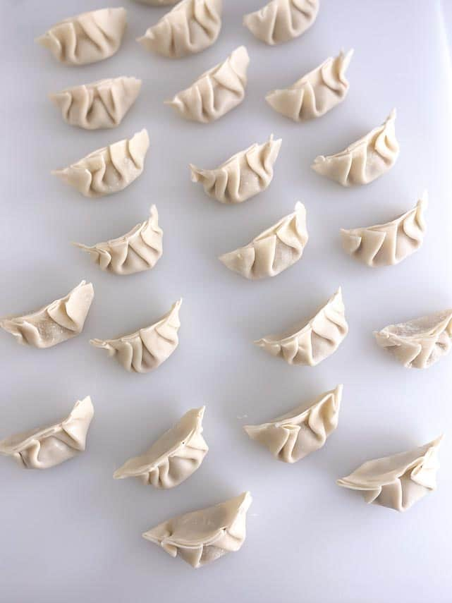 pleated dumplings on white board ready to cook