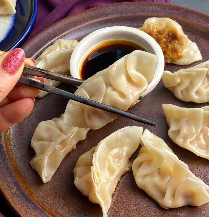 pork dumplings held between chopsticks, hovering over sipping sauce