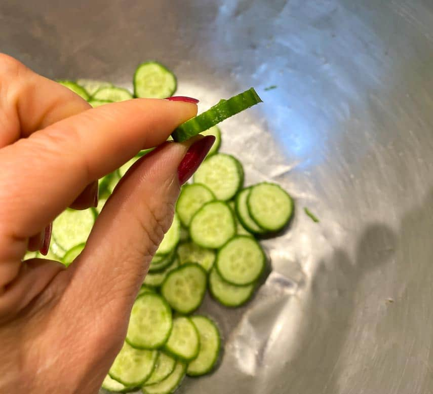 thinly sliced cucumber held in hand