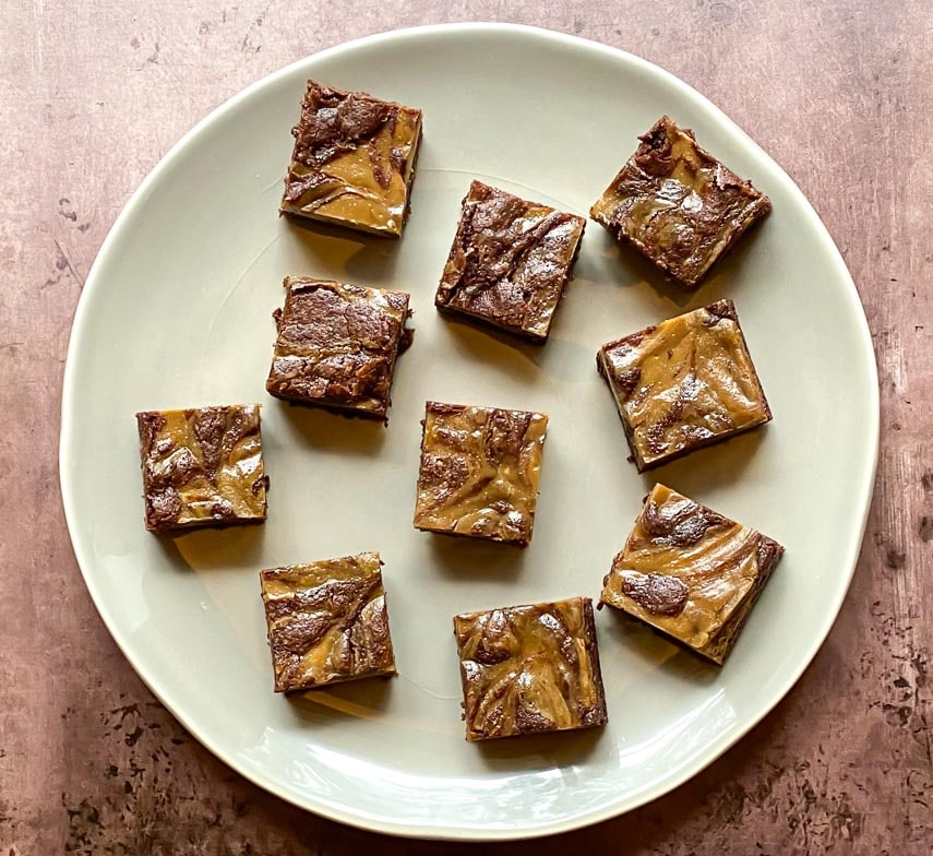 very close overhead of espresso cream cheese brownies on light plate and brown background