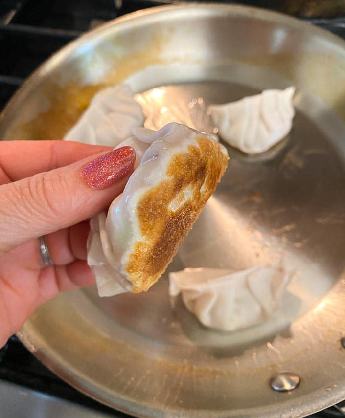woman's hand holding dumpling with seared bottom