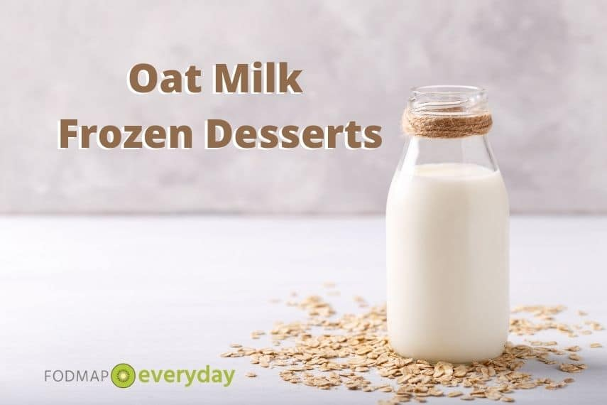 a side shot of a glass milk bottle filled with oat milk with oats scattered around it