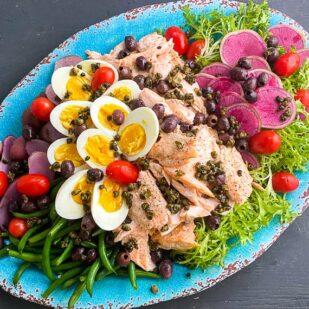 Low FODMAP Salmon Salade Nicoise on oval turquoise platter