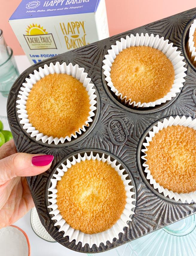 baked cupcakes in pan held in hand