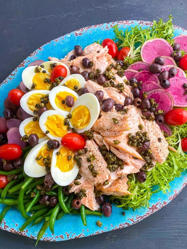 closeup of low FODMAP Salmon Salade Nicoise on turquoise platter