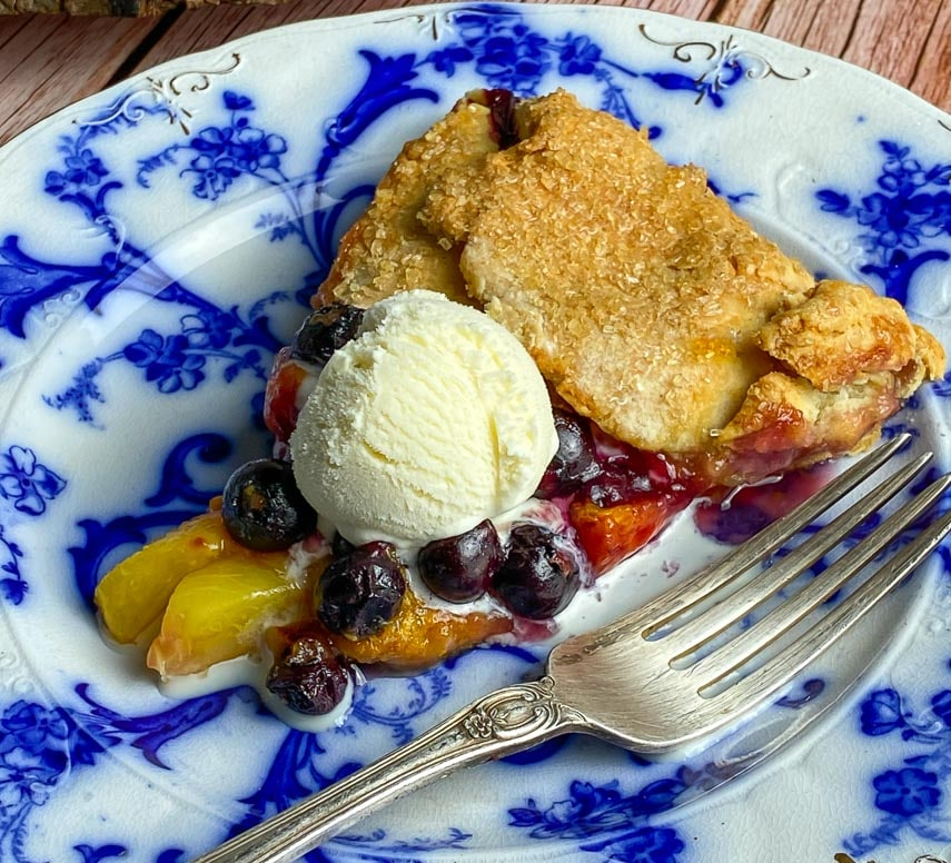 closeup of wedge of peach blueberry crostata on decorative blue and white plate