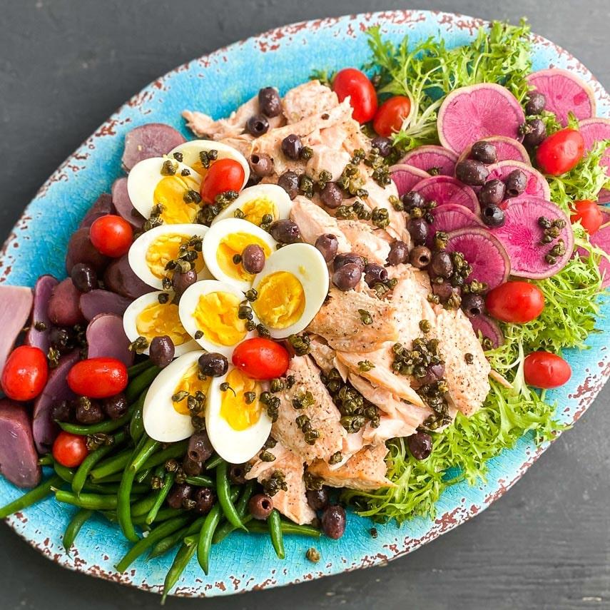 closeup salmon salade nicoise on oval platter