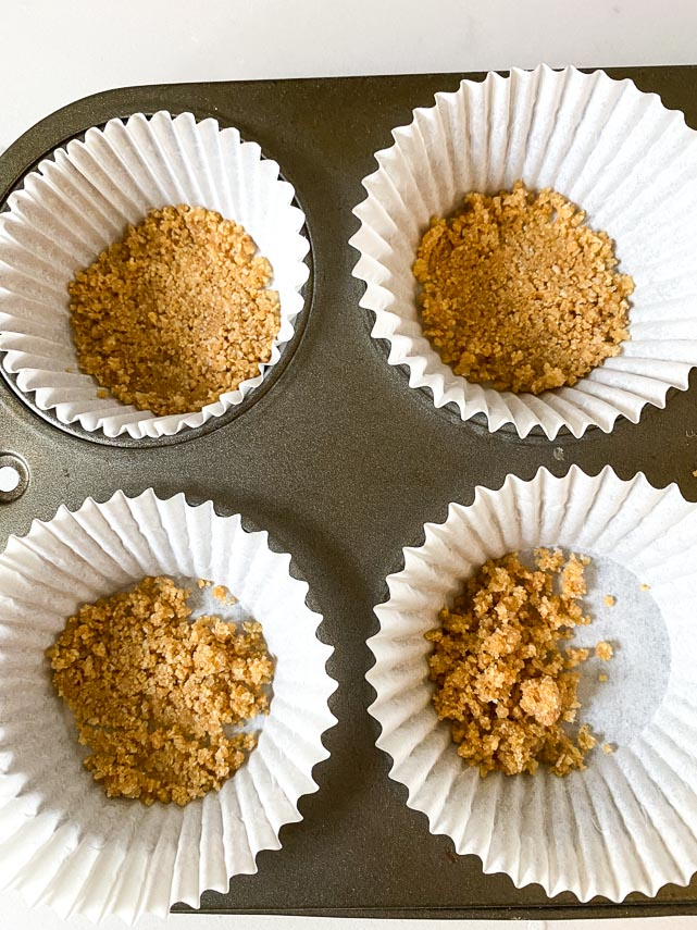 creating graham cracker crust in fluted paper liners in cupcake pan