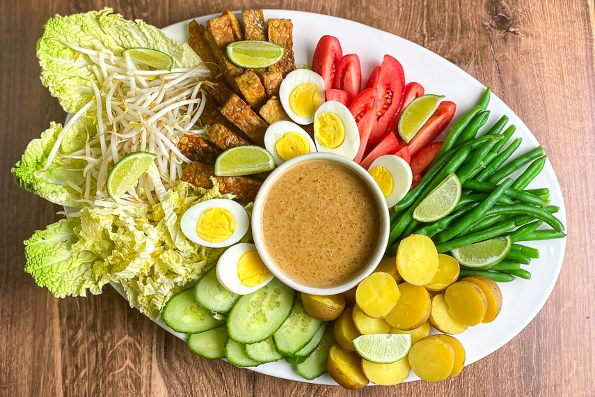 main image of white oval platter holding Low FODMAP Gado-Gado with dishes of shrimp crackers alongside on wooden surface