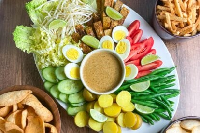 overhead horizontal image of white oval platter holding Low FODMAP Gado-Gado with dishes of shrimp crackers alongside on wooden surface
