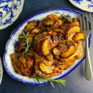 overhead image of Low FODMAP Balsamic Chicken with peaches and rosemary on decorative blue and white oval platter