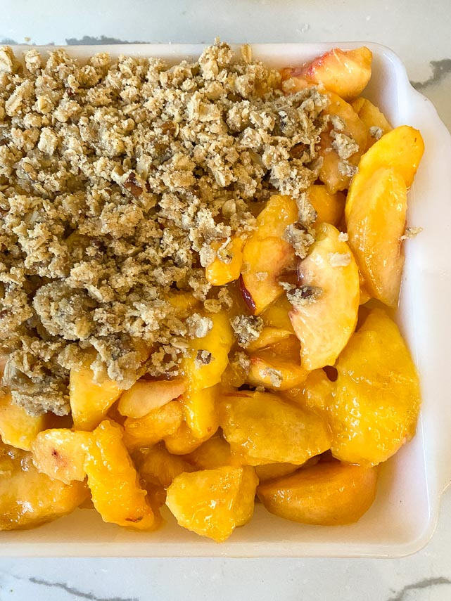 peach crisp filling in square baking dish partially covered with crisp topping
