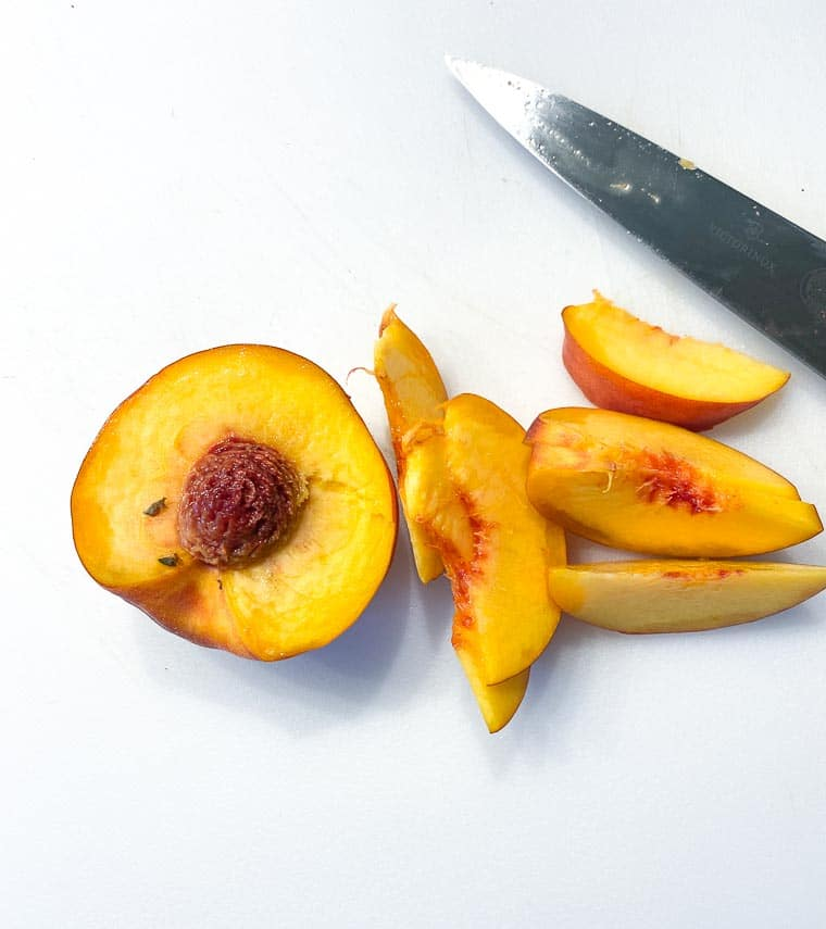 peach on white cutting board, half and wedges