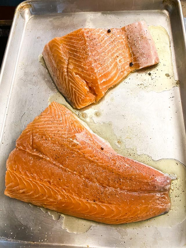 raw salmon fillet brushedd with caper oil on rimmed sheet pan