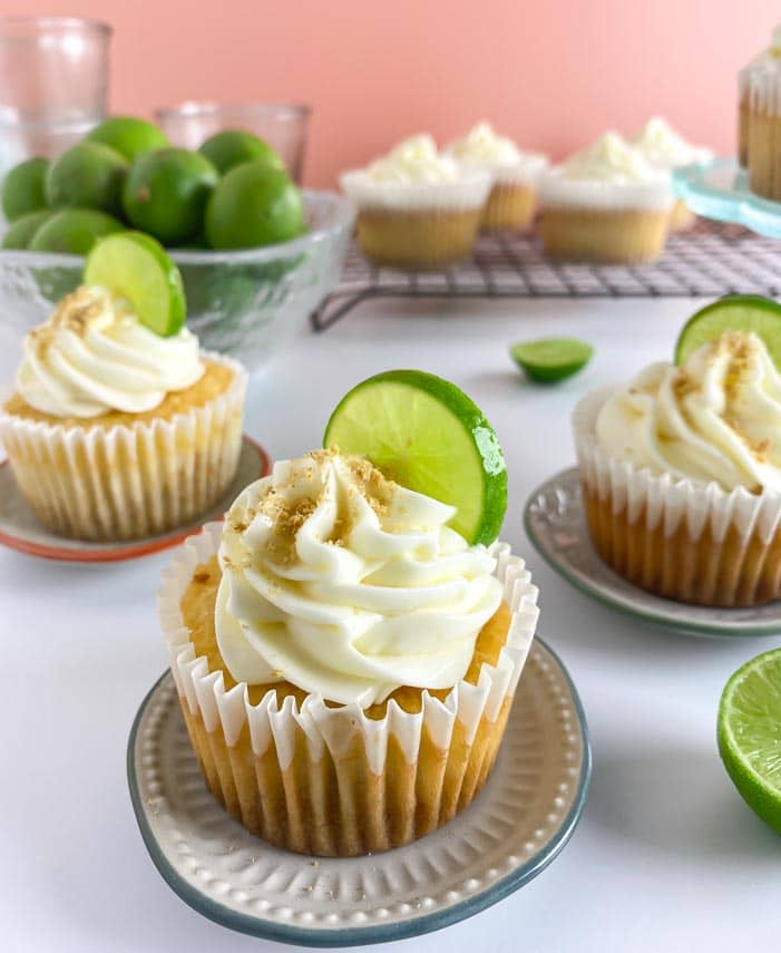vertical closeup of Low FODMAP Key Lime Cupcakes on table and rack