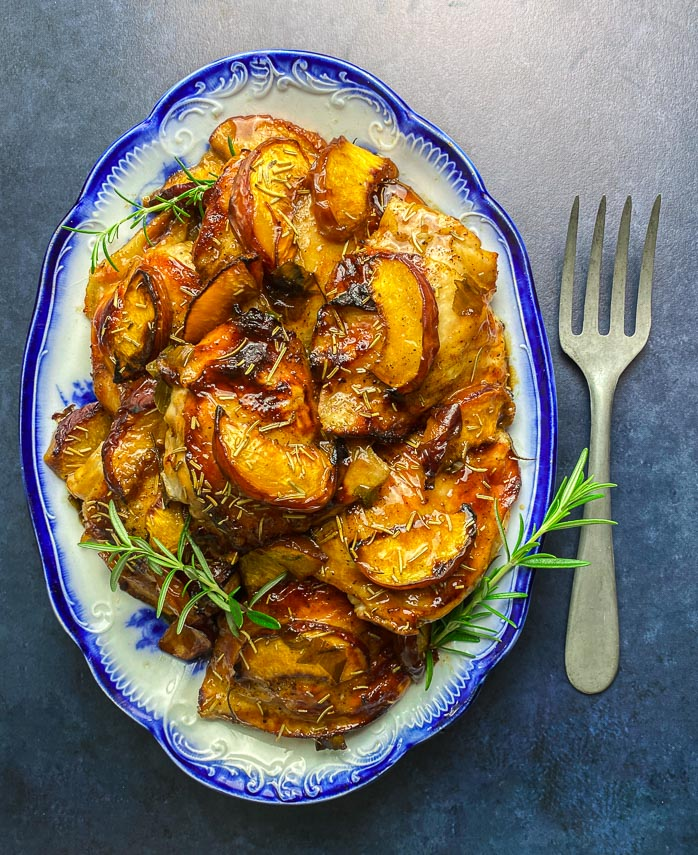 vertical image of ow FODMAP Balsamic Chicken with peaches on blue and white platter with fork