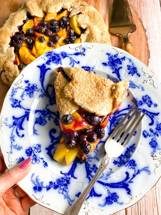 vertical image of wedge of peach blueberry crostata on blue and white plate, held by woman's hand