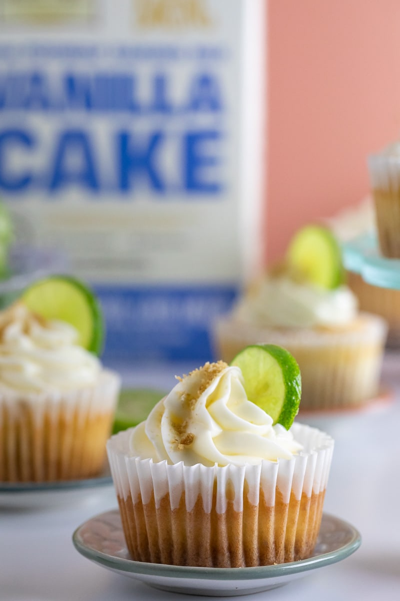 vertical low FODMAP Key Lime Cupcakes on tiny plate; boxed cake mix in background